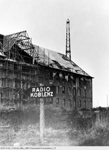 """Bereits im Juli 1945 begannen die Franzosen mit dem Aufbau des sog. Radio Koblenz in der ehemaligen Falkensteinkaserne. Im Hintergrund der nahezu unbeschädigte 107 m hohe Sendeturm, über den ab 14.10.1945 das etwa 6-8-stündige Tagesprogramm ausgestrahlt wurde. © SWR/Tschira,  Bild: SWR/Tschira"""" (S2). SWR-Pressestelle / Fotoredaktion, Baden-Baden, Quelle: """"obs/SWR - Südwestrundfunk"""""""